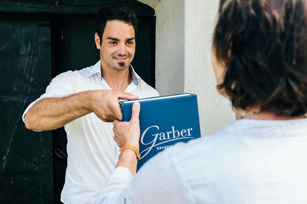 Garber Patrick mit Weinkarton und Kundin